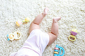 Close-up of baby body and legs with lots of colorful rattle toys.