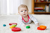 Cute baby girl playing with colorful wooden rattle toy
