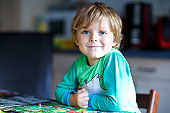 Little blond kid boy playing together board game at home. Funny child having fun
