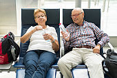 Seniors Taking on the World, happy tourist couple waiting in airport seats
