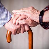Senior couple holding hands on crutch