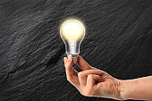 Holding a glowing light bulb in front of dark stone