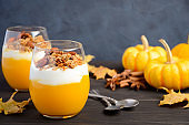 Pumpkin dessert with yogurt and homemade granola on dark wooden table