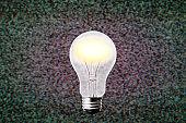 Illuminated a illuminated floating light bulb against abstract background