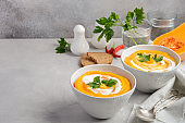 Pumpkin soup with cream and parsley on a grey concrete or stone background
