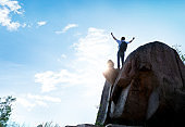 Man at mountain top with arms outstretched