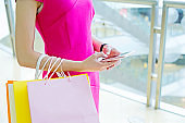 Young shopping woman using a smartphone