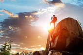 Hiker on top of mountain at sunset