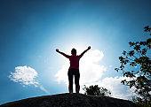 Woman on the top of mountain peak rock