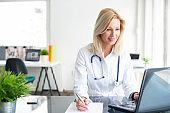 Confident female doctor at office desk