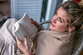 Young beautiful woman sits and reads a book on a terrace covered with a blanket