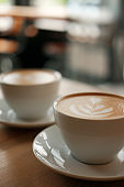 Two white cups of fragrant cappuccino stand on a wooden table. Coffee with milk  on the table, front view.
