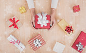 hand holding gift box with decorations and snowflake on wooden board.