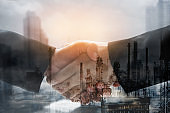 Double exposure business worker with graph finance and factory construction. concept success investment.