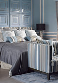 Light blue romantic style bedroom with reading lamp and comfortable sofa