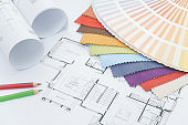 Interior designer working desk with drawing, fabric sample, color pencil and color palette