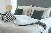 Messy bed with pillows in modern interior  bedroom