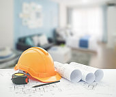 architectural blueprint with safety helmet and tools over blue color scheme bedroom with sofa