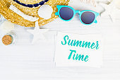 Blue summer time word on white card at wood table with sunglasses,straw hat,starfish,glass bottle top view,Vacation concept.