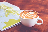 White coffee cup with latte art with travel map on brown wood table,Leisure activity