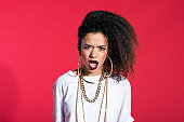 Angry latin young woman in hip-hop style against red background