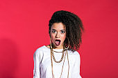 Surprised latin young woman in chola style against red background