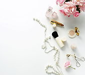 Flat lay, top view feminine desk, workspace , female make up accessories and bouquet roses.Beauty blog