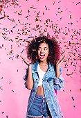 Portrait of excited young afro woman among confetti
