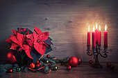 Chhristmas still life with poinsettia and seasonal decorations on wood