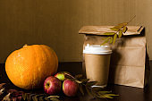 Autumn business lunch, still life with pumpkin, apple and foliage