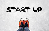 Foot and start up word on cement floor background, business concept