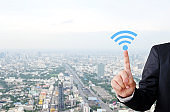 Businessman hand pointing wifi icon over blur city scrape background, internet of things concept