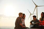 Group of friends having fun on wind turbine.