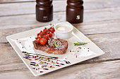Appetizing ribeye steak sprinkled with spices.