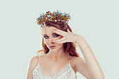 Crowned beauty queen. Blonde curly hair woman fashion model girl purple makeup eye shadow crystals crown looking at camera showing beige nails manicure color in set with lipstick isolated light green
