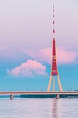 Riga, Latvia. Famous Landmark Television Tower In Pink Purple Sunset Or Sunrise Colors Sky.