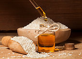 Fresh sesame oil in a glass bottle and seeds in wooden bowl and spoon