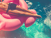 Woman floating on a pink inflatable in swimming pool.