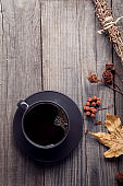 cup of hot espresso among autumn plants on wooden vintage table,