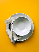 empty plate for soup on a yellow background