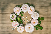 pink roses wrealh with small wooden hearts on the wooden table, top view with copy space