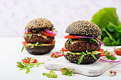 Black big sandwich -  black hamburger with juicy beef burger, cheese, tomato,  and red onion on light background.
