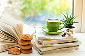Coffee cup, open book, cookies and flower on window with bokeh. Reading and breakfast. Concept warm and cozy home decor