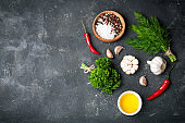 Herbs and spices cooking on stone table. Parsley, dill, garlic and pepper. Seasoning ingredients for cooking. Top view with copyspace