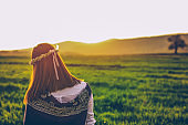 Beautiful image of hipster girl sitting in the grass field on a sunny summer day