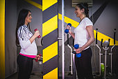 Pregnant woman exercising at the gym with fitness instructor and lifting weights
