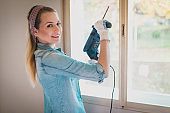 Young woman with electric drill renovating home