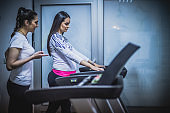 Pregnant woman exercising at the gyim with a help of fitness instructor