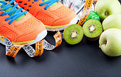 Sport shoes, fruits,  bottle of water and measuring tape on dark background. Sport equipment. Concept healthy life, sports and diet