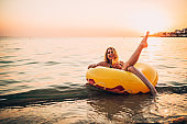Young woman floating on water and drinking cocktail tequila sunrise on a beautiful summer day